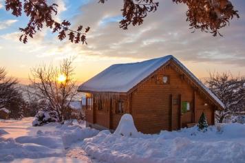 Le chalet sous la neige et couché de soleil